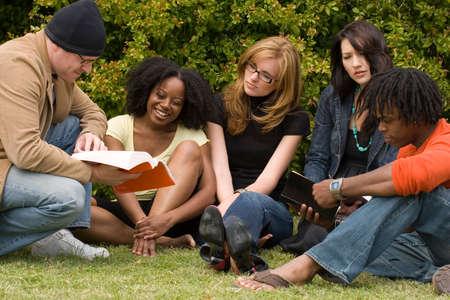 Zróżnicowana grupa ludzi czytających i studiujących.
