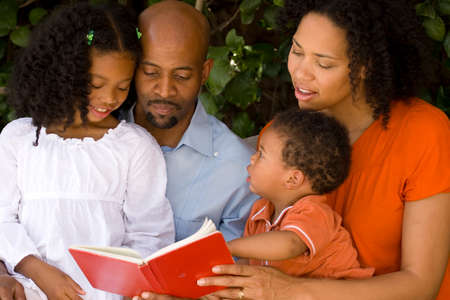 Loving African American parents reading with their kids. Foto de archivo