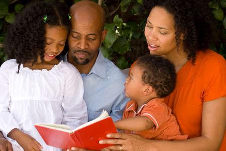 Liefhebbers van Afrikaanse Amerikaanse ouders die met hun kinderen lezen. Stockfoto