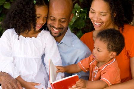 愛するアフリカ系アメリカ人の両親は彼らの子供を読みます。 写真素材 - 71641807