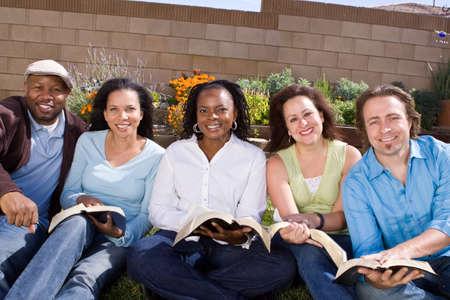 Diverse groep van mensen die het lezen en studeren.
