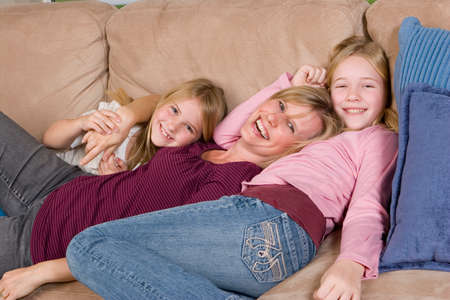 Loving mother spending time with her daughters at home.