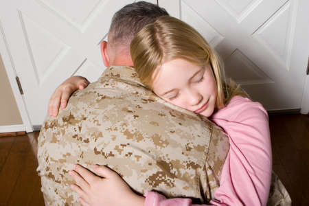 adoring: Happy young girl hugging her father in uniform