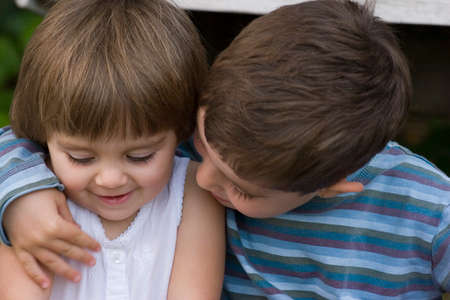 Portrait of a happy brother and sister hugging.