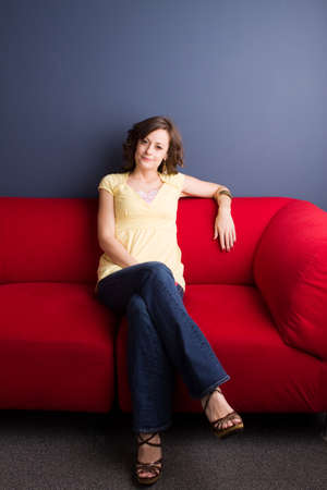 Happy woman sitting in a red chair.