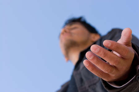 Hispanic man with open arm in prayer.
