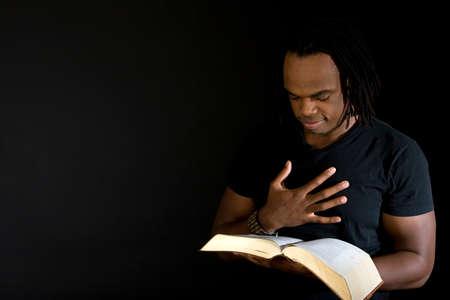黒に分離された聖書を読んでいる人。