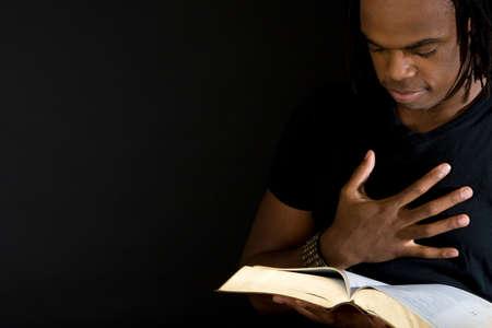 Uomo che legge una bibbia isolata sul nero.