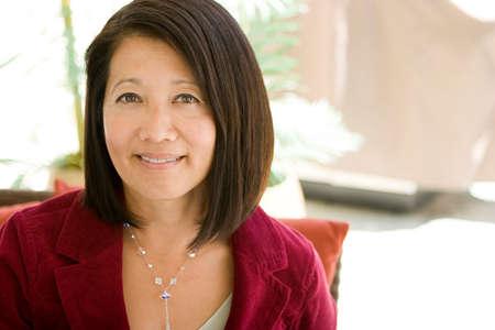 Sorridente donna asiatica fiduciosa e matura sorridente