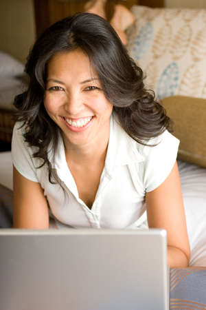 southern european descent: Woman Relaxing On Bed Using Laptop Computer