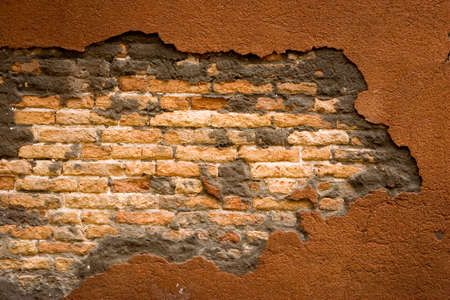 cracked concrete: Cracked concrete wall with exposed brick. Stock Photo