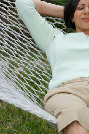 one person only: Mature African American woman relaxing in a hammock.