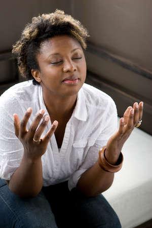 Mujer afroamericana en pensamiento profundo rezando.