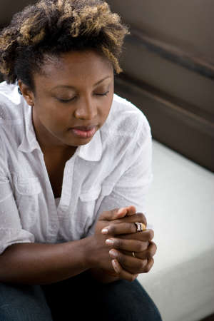 African American woman in deep thought praying.