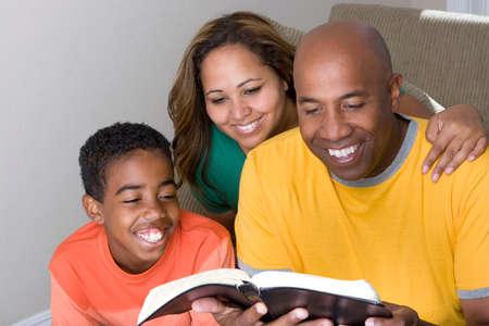 アフリカ系アメリカ人の多文化家族聖書を読みます。 写真素材