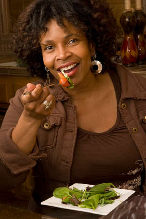 vegtables: African American woman smiling eating a salad.