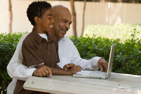 African American grandfather and grandson working on the computer.