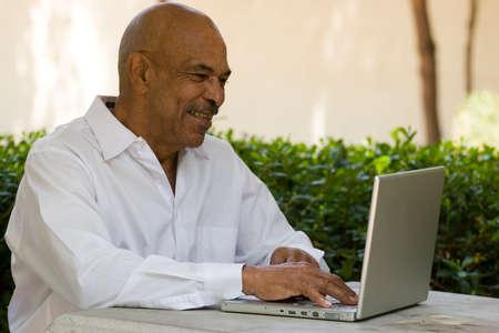 랩톱 컴퓨터에서 작업하는 흑인 노인 스톡 콘텐츠