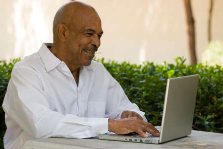 랩톱 컴퓨터에서 작업하는 흑인 노인