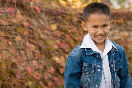 Happy Asian little boy smiling standing outside.