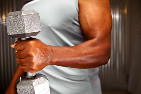 Mature African American lifting weights and exercising. Imagens