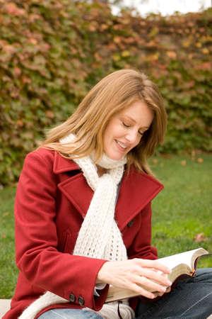 Beautiful woman sitting outside reading wearing a red coat. Reklamní fotografie