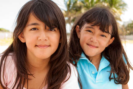 Cute sisters playing at the beach on the sand. Stock Photo