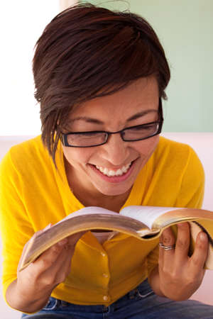 Happy woman sitting inside reading a book. Stock Photo