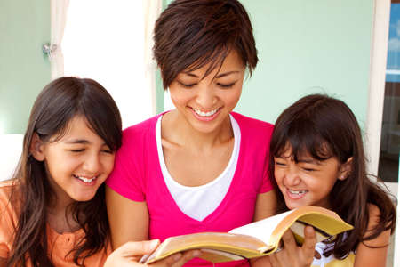 Mother spending time reading with her daughters.