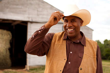 African American cowboy smiling and tipping his hat