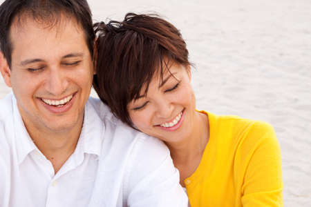mixed marriage: Happy couple laughing and talking at the beach.