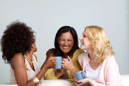 Diverse group of women talking and drinking coffee.