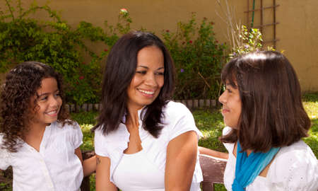 age 35 40 years: Happy Hispanic mother and daughters smiling.