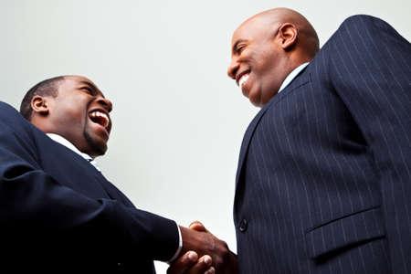 アフリカ系アメリカ人のビジネスマンは、白で隔離の手を振ってします。