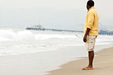 disbelief: African American man walking on the beach. Stock Photo