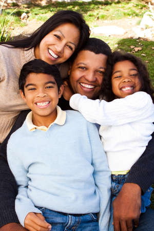 Biracial family laughing and smiling outside.