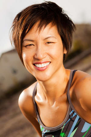 Fit Asian woman smiling outside.