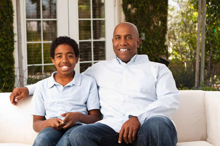 role model: African American father and son talking and laughing.