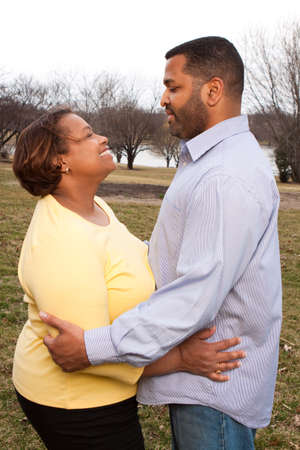 carrying: Happy African American couple hugging outside. Stock Photo