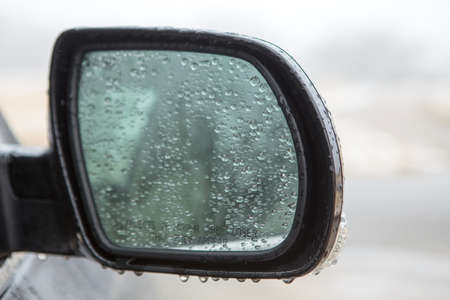 Car rear view mirror. Rainy day.