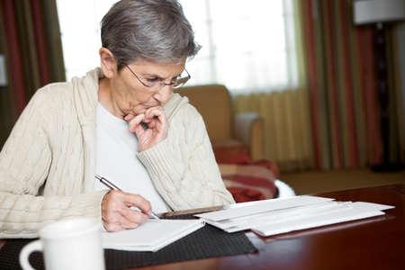 Senior Woman Paying Bills Standard-Bild