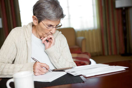 Senior Woman Paying Bills Imagens