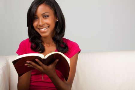 African American teenage girl reading.