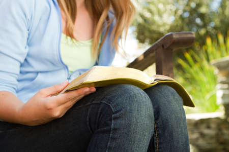 Young teen girl outside reading in the backyard. Standard-Bild