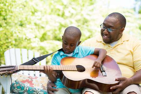 Vater Teaaching sein Sohn, um die Gitarre zu spielen. Standard-Bild - 87985127