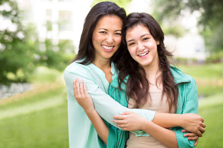 southern european descent: Asian mother laughing and huging her child. Stock Photo
