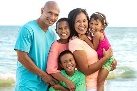 Familia feliz jugando en la playa.