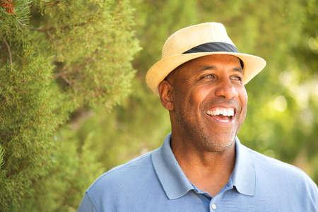 밖에 서 그의 모자 팁을 아프리카 계 미국인 남자.