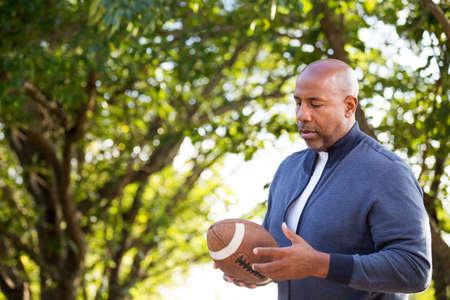 Mature African American man holding a football.