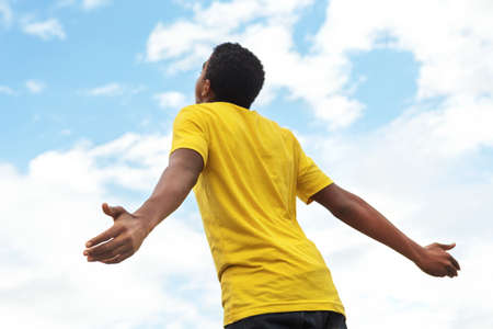 African American young teen boy with open hands to the sky.